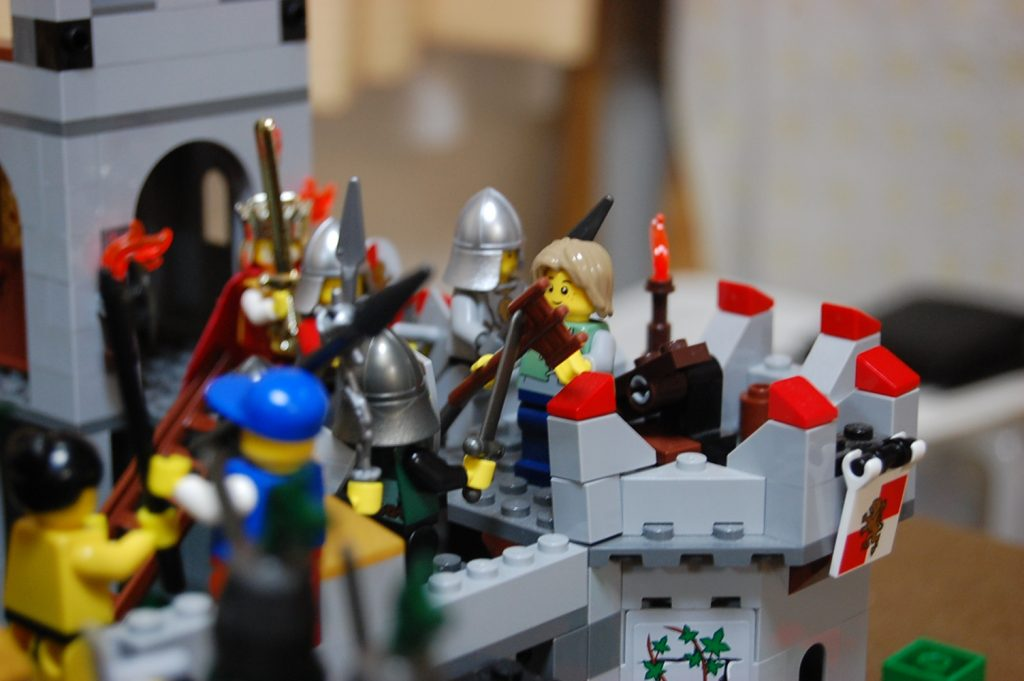 Lego Red Lion Knights back up a minifig peasant armed with a pitchfork.